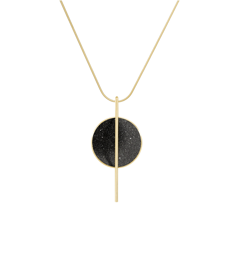 The Linnea 14k necklace features black concrete and the sparkle of embedded diamond dust set into a 14 karat gold dome intersected by a steel post suspended by a gold cable.