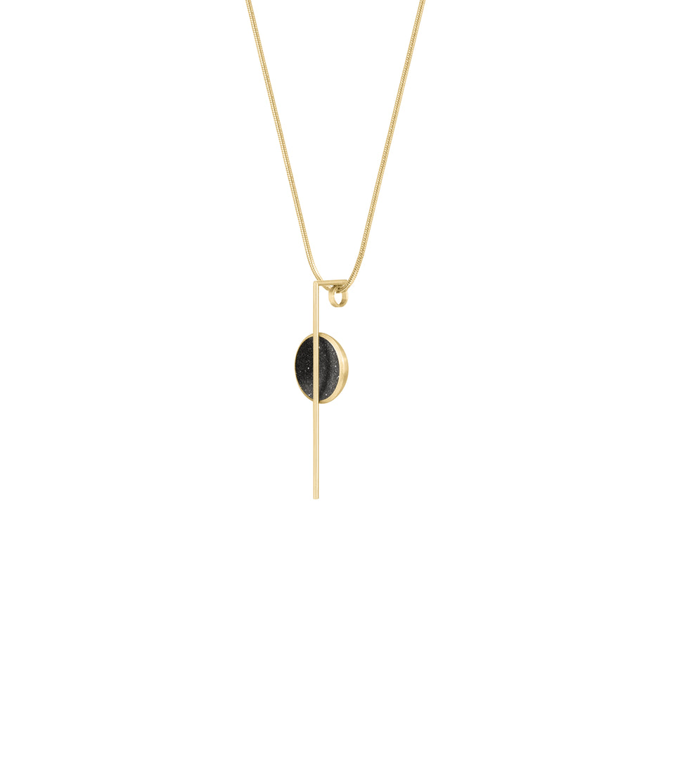The Linnea Minor 14k necklace features black concrete and the sparkle of embedded diamond dust set into a 14 karat gold dome intersected by a steel post and suspended by a gold cable.