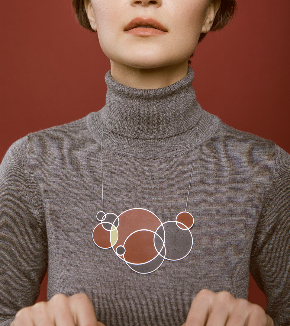 Model wears large circular motif necklace inspired by Frank Lloyd Wright's drawing March Balloons. Wearable architecture designed and made with concrete and stainless steel.