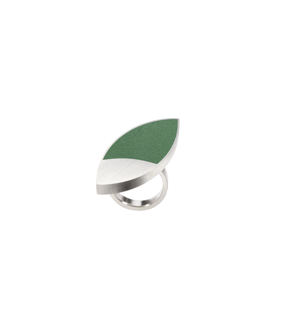 Concrete tinted with custom Cypress Green color. Set into leaf-shaped stainless steel ring inspired by overlapping circles in Frank Lloyd Wright's March Balloons artwork.