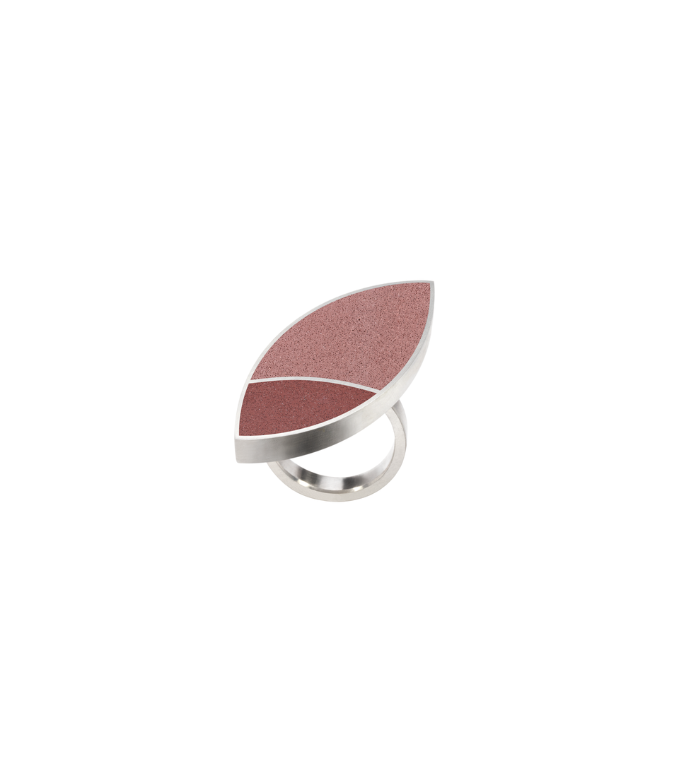 Concrete tinted in custom Taliesin Red. Set into leaf-shaped stainless steel ring inspired by resulting shapes from overlapping circles in Frank Lloyd Wright's March Balloons artwork.