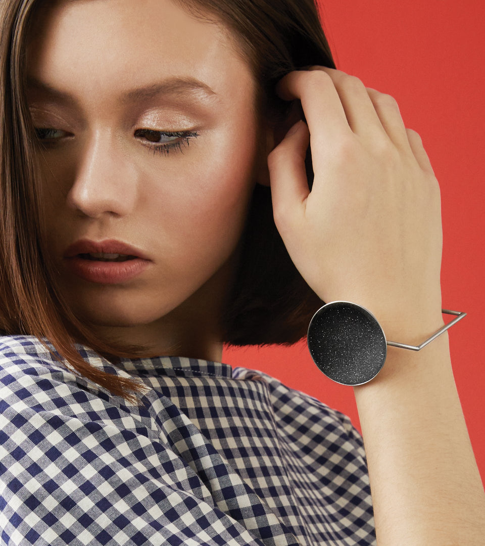 Quadra bracelet is Bauhaus design inspired jewelry featuring diamond dust infused black concrete set into a handmade stainless steel dome suspended from a steel minimalist square frame.
