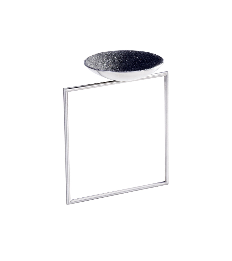 The minimalist Quadra bracelet sparkles with diamond dust embedded into black concrete set into a stainless steel dome architecturally positioned onto a steel square frame.