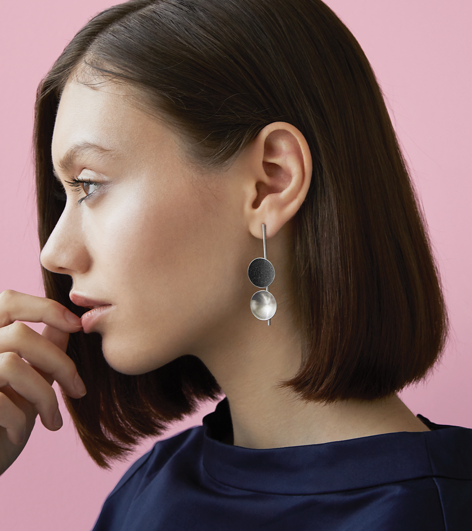 Bauhaus inspired Freya earrings feature two double stainless steel domes, one lined with diamond dust infused black concrete both architecturally supported an elegant hanging steel post.