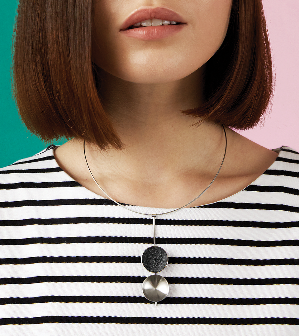 Close-up of the Bauhaus inspired Freya necklace featuring two larger double stainless steel domes, one lined with the sparkle of diamond dust infused black concrete both architecturally supported by an elegant hanging steel post and cable.