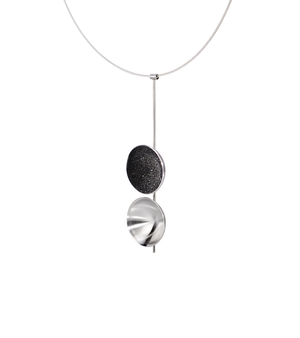 Side view of the Freya statement necklace featuring two double stainless steel larger domes, one lined with diamond dust infused black concrete both architecturally supported an elegant hanging steel post.