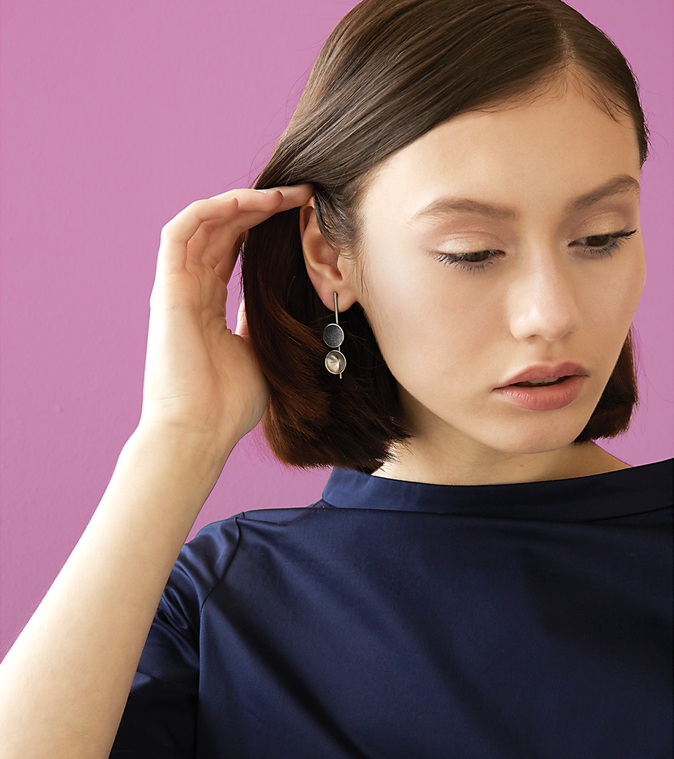Bauhaus inspired Freya Minor earrings feature two smaller double stainless steel domes, one lined with diamond dust infused black concrete both architecturally supported an elegant hanging steel post.