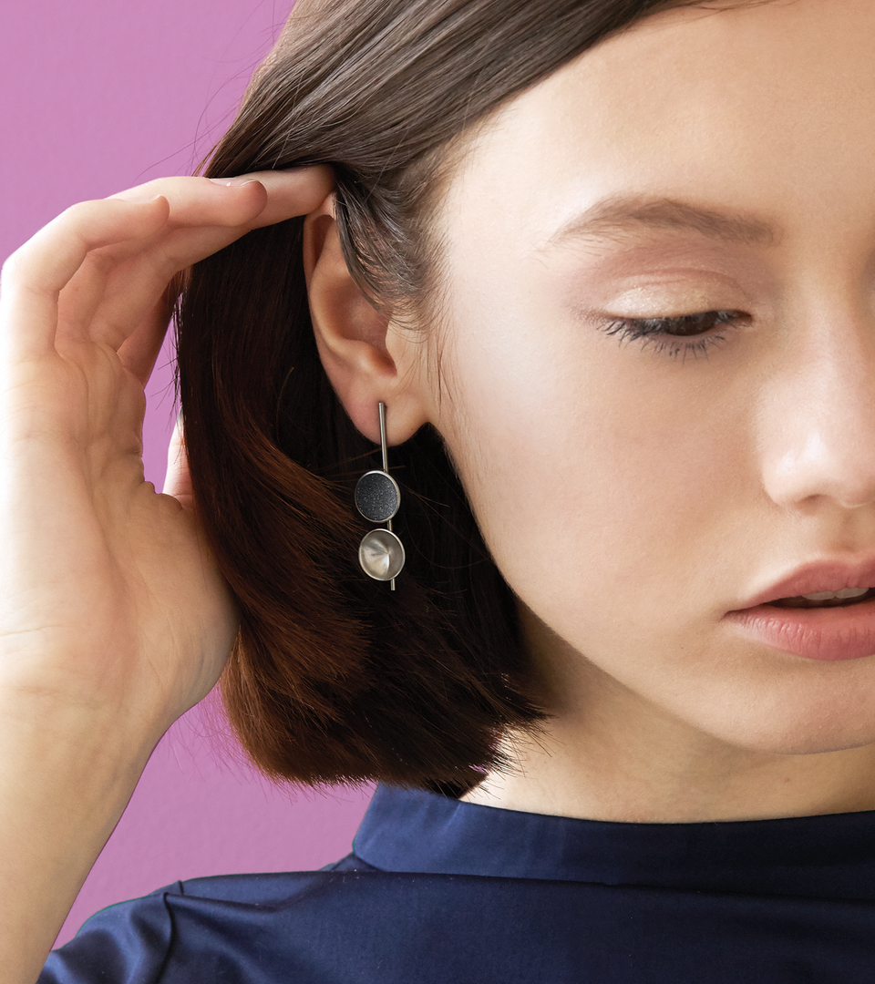 Close-up of Bauhaus inspired Freya Minor earrings feature two smaller double stainless steel domes, one lined with diamond dust infused black concrete both architecturally supported an elegant hanging steel post.