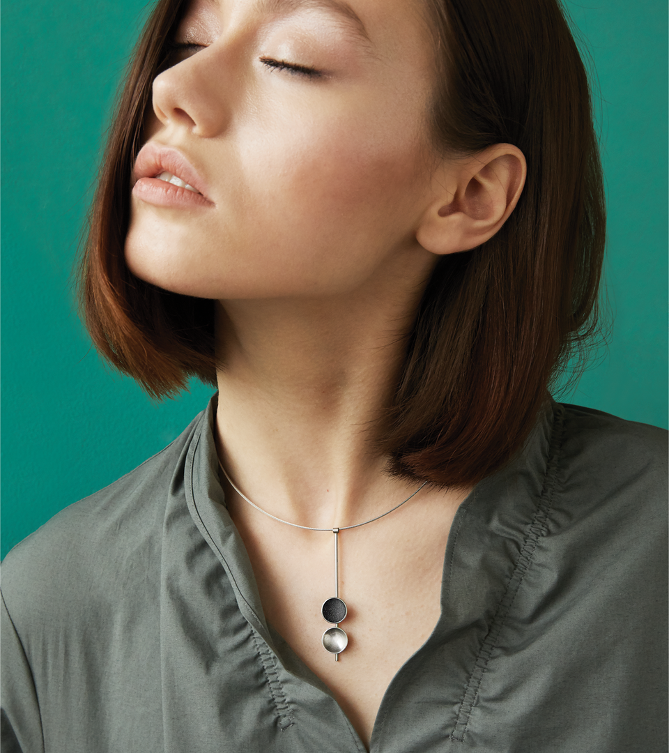 The Bauhaus inspired Freya Minor necklace features two double stainless steel domes, one lined with diamond dust infused black concrete both architecturally supported by an elegant hanging steel post.