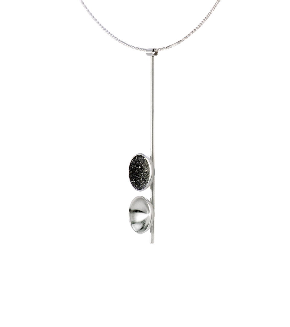 Side view of the Freya Minor modern necklace features two double stainless steel domes, one lined with diamond dust infused black concrete both architecturally supported an elegant hanging steel post.