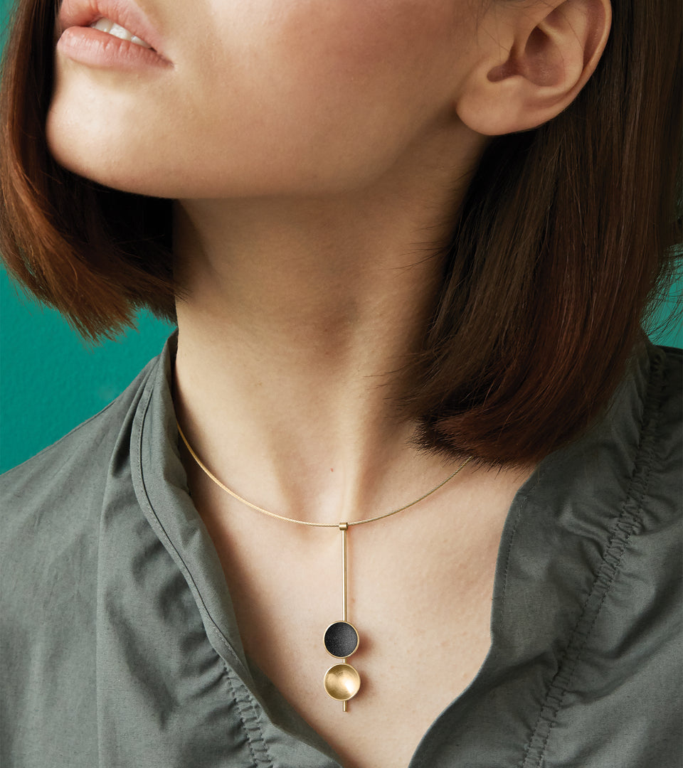 The Freya Minor modern necklace features two double 14 karat gold domes, one lined with diamond dust infused black concrete both architecturally supported an elegant hanging 14k gold post.
