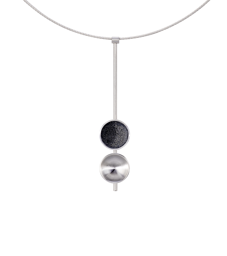 The Freya Minor modern necklace features two double stainless steel domes, one lined with diamond dust infused black concrete both architecturally supported an elegant hanging steel post.