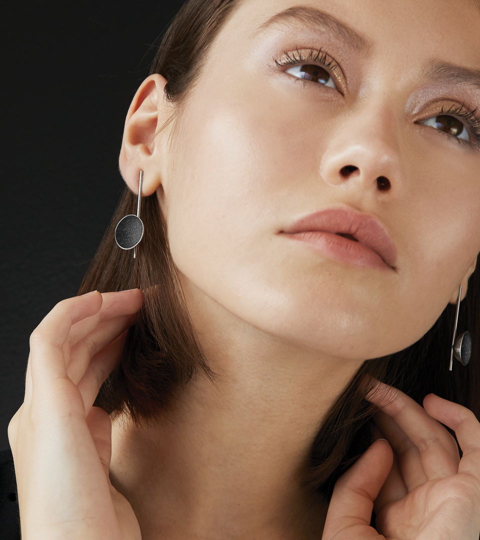 Close up of Bauhaus designed Inspira earrings sparkle with diamond dust and black concrete set into a stainless steel dome architecturally suspended on top of a minimalist steel post.