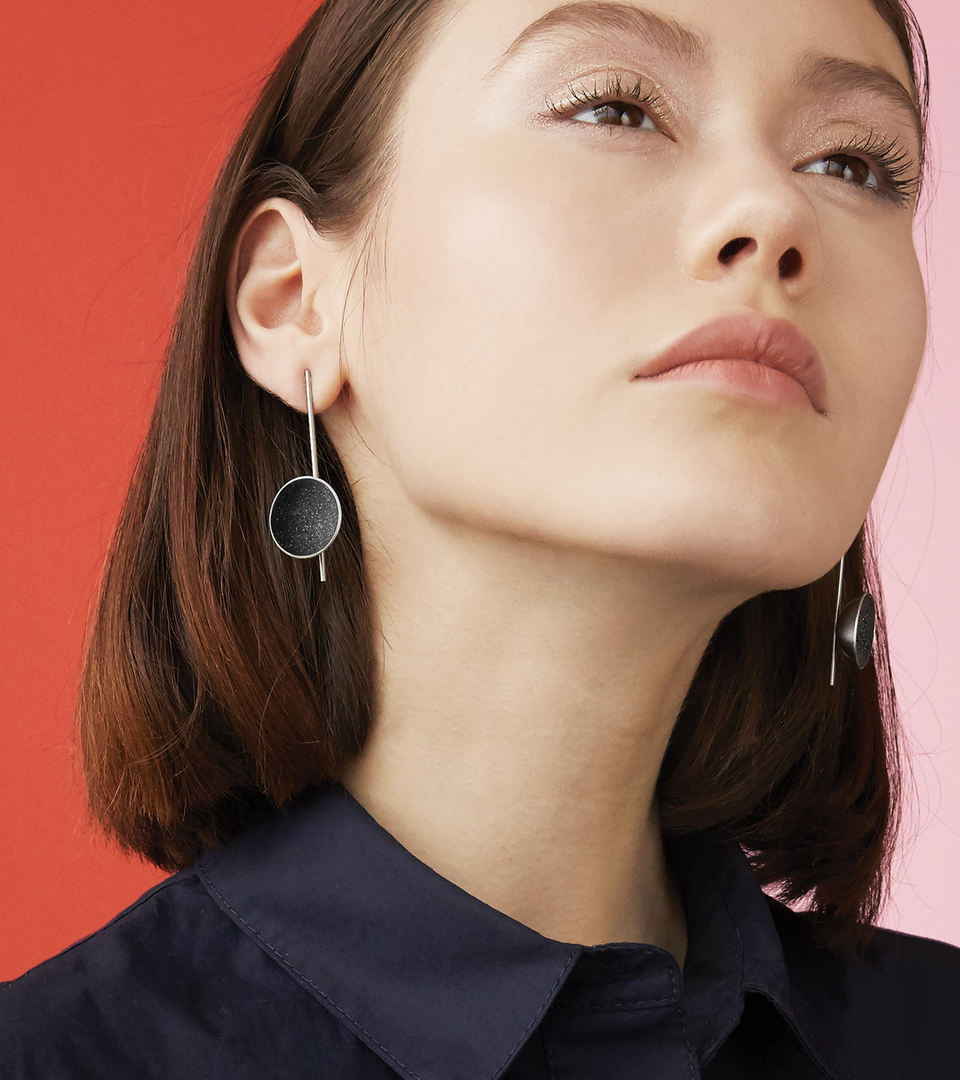 Inspira Major earrings feature authentic diamond dust embedded into a medium sized concrete lined stainless steel dome architecturally positioned onto a suspended minimalist steel post.