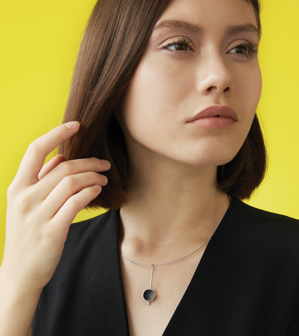 Inspira Minor minimalist necklace sparkle with diamond dust and black concrete set into a stainless steel dome suspended on top of an elegant steel post.