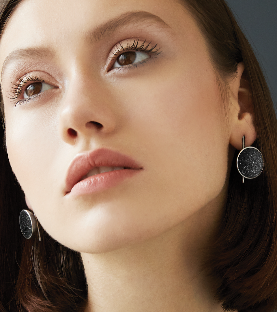 Close up of modern Juno Major earrings sparkle with diamond dust and black concrete lined stainless steel dome a minimalist steel post.