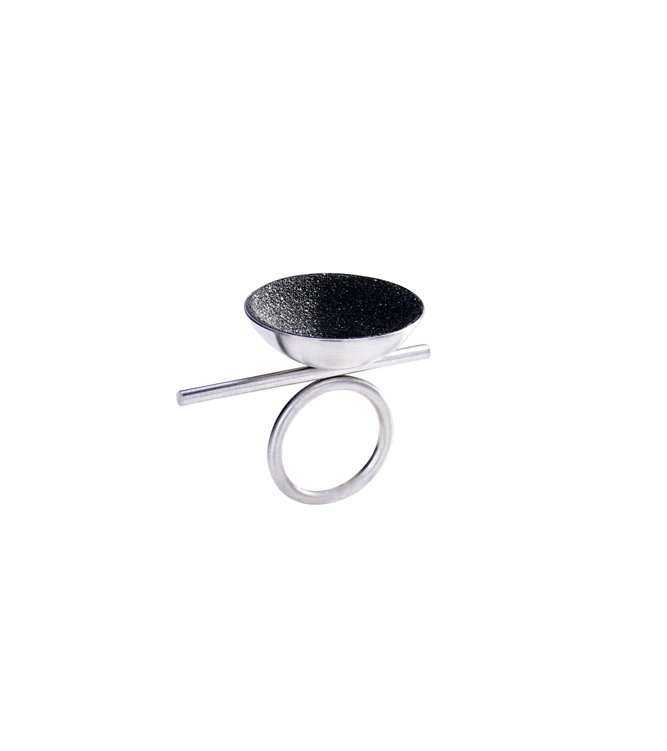 Juno Major ring features with diamond dust infused concrete lining a stainless steel dome perched off center of its supporting steel rod round steel ring.