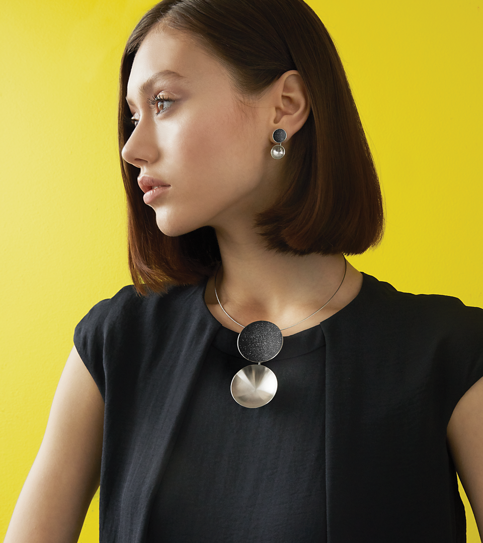 The Bauhaus inspired Ligo Major necklace features two stainless steel domes, one lined with the sparkle of diamond dust infused black concrete both supported by an elegantly hanging steel post.
