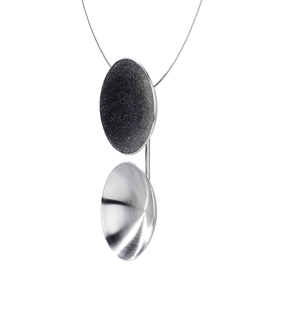 The side view of the Ligo Major necklace features two statement making double stainless steel domes, one lined with diamond dust infused black concrete both architecturally supported vertically by an elegant steel post.