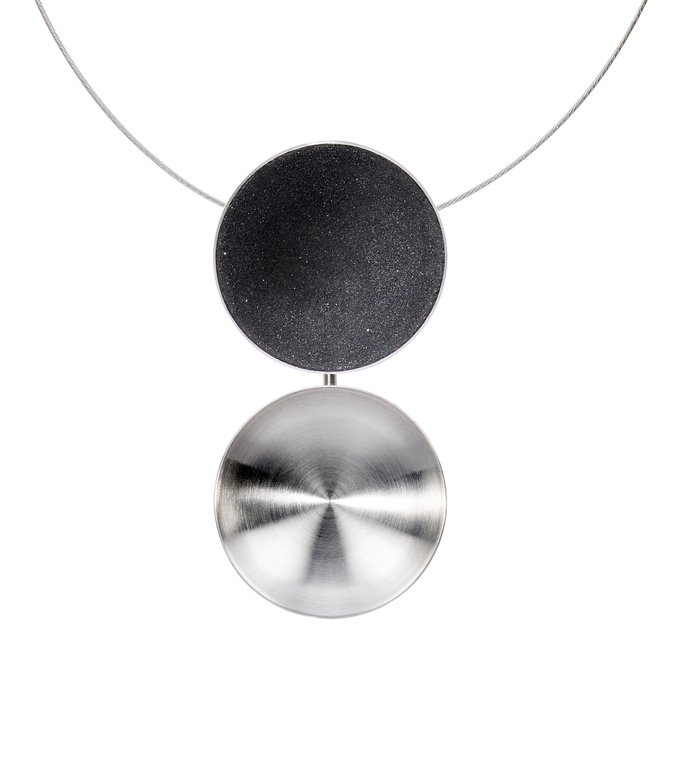The Ligo Major necklace features two statement making double stainless steel domes, one lined with diamond dust infused black concrete both architecturally supported vertically by an elegant steel post.