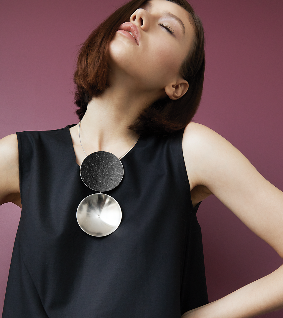 The Ligo Max statement necklace features two stainless steel domes, one lined with diamond dust infused black concrete both supported a vertically hanging steel post.
