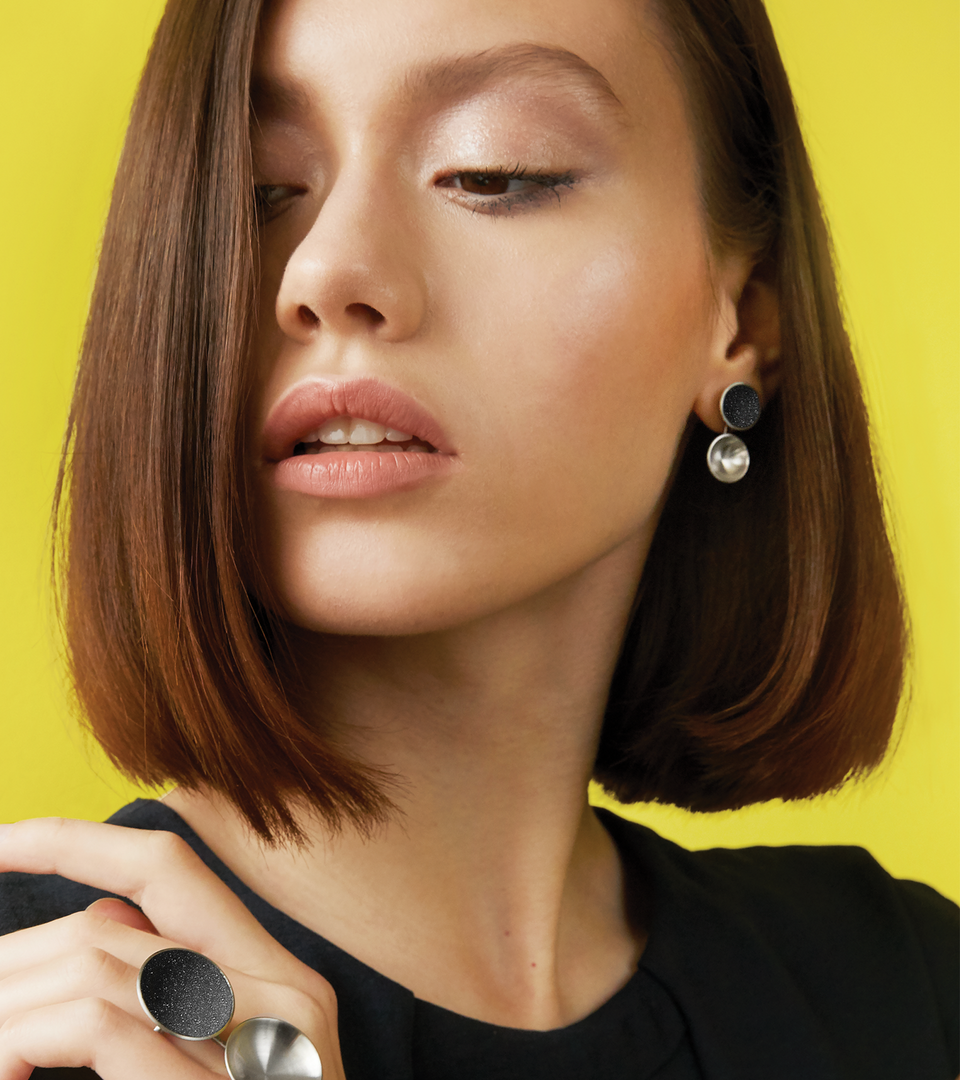 Minimalist Ligo Minor earrings are designed with two stainless steel domes, one lined with diamond dust infused black concrete both supported by a small steel post.