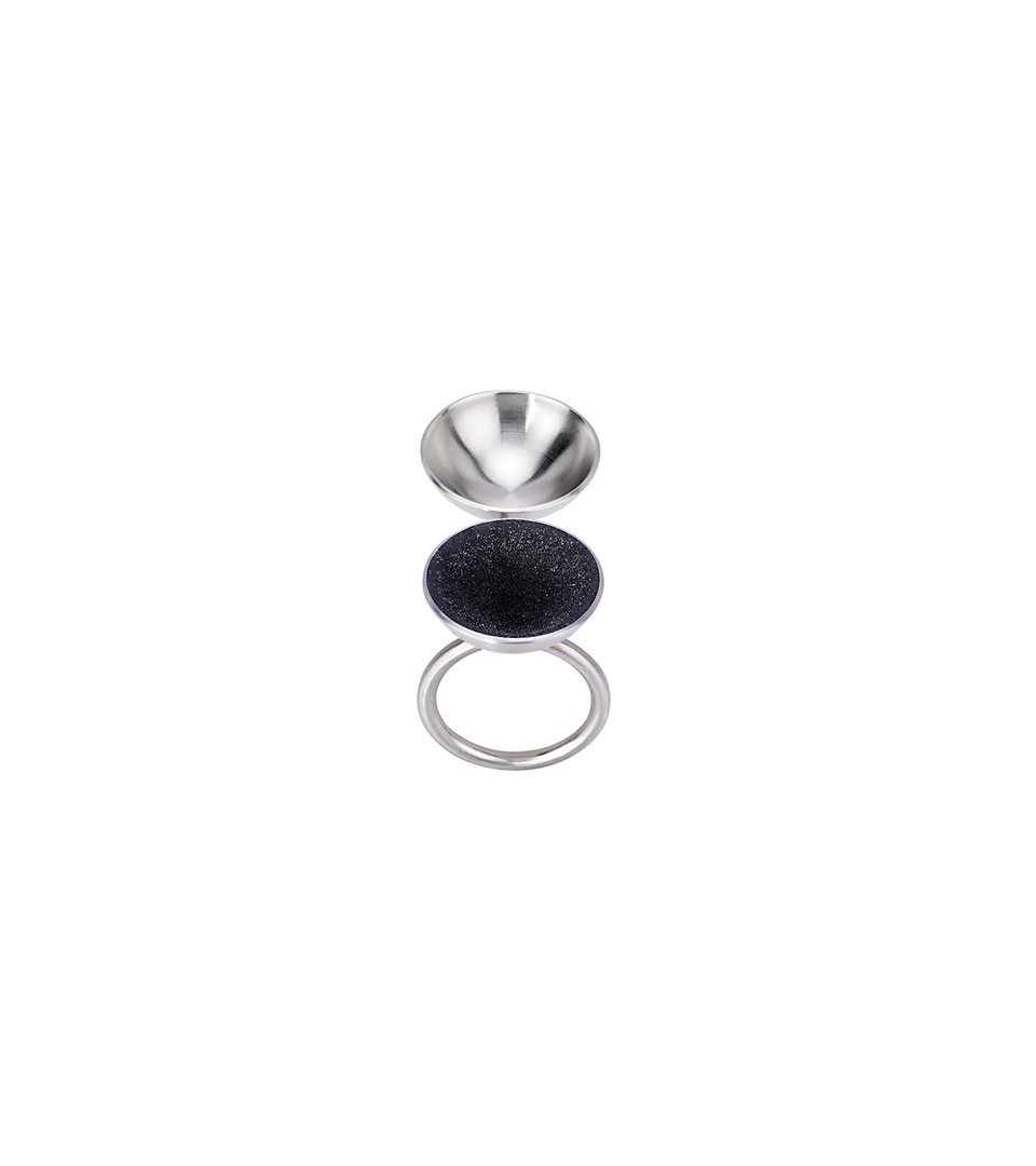 Top view of the Ligo Minor ring designed with two stainless steel domes, one lined with diamond dust infused black concrete both cantilevered on top a horizontal steel post from a round steel ring.