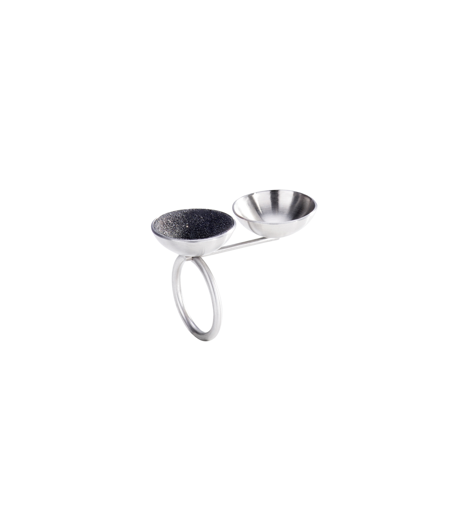 The Ligo Minor ring is designed with two stainless steel domes, one lined with diamond dust infused black concrete both architecturally positioned on top a horizontal steel post cantilevered from a minimalist round steel ring.