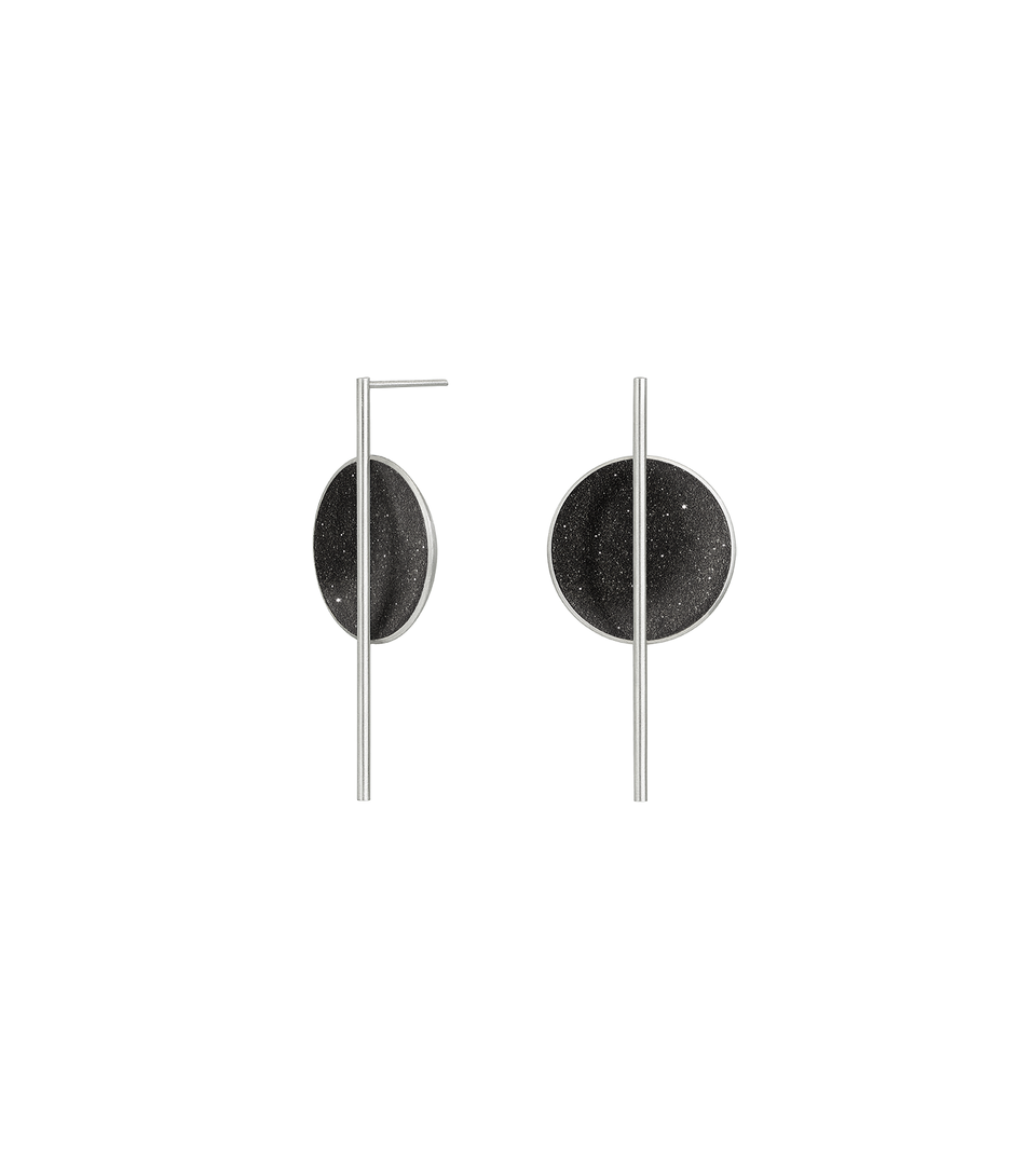 The Linnea earrings sparkle with diamond dust and black concrete set into a stainless steel dome architecturally suspended behind a minimalist steel post.