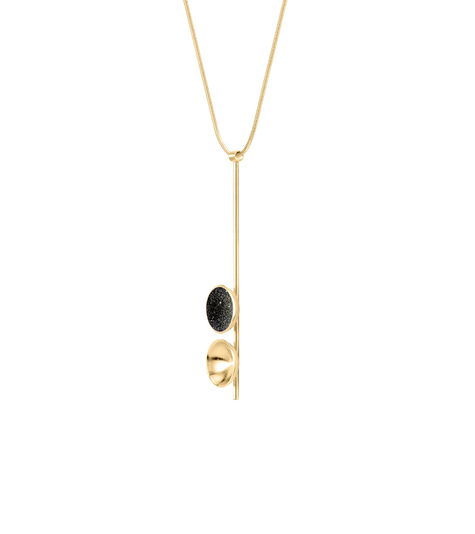 Side view of the modern Freya Minor necklace features two double solid 14 karat gold domes, one lined with diamond dust infused black concrete both architecturally supported an elegant hanging 14k gold post.