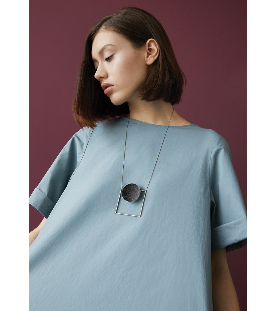 Architectural necklace combines the geometry of a large stainless steel dome lined with the sparkle of diamond dust encrusted concrete suspended onto a minimalist steel square frame.