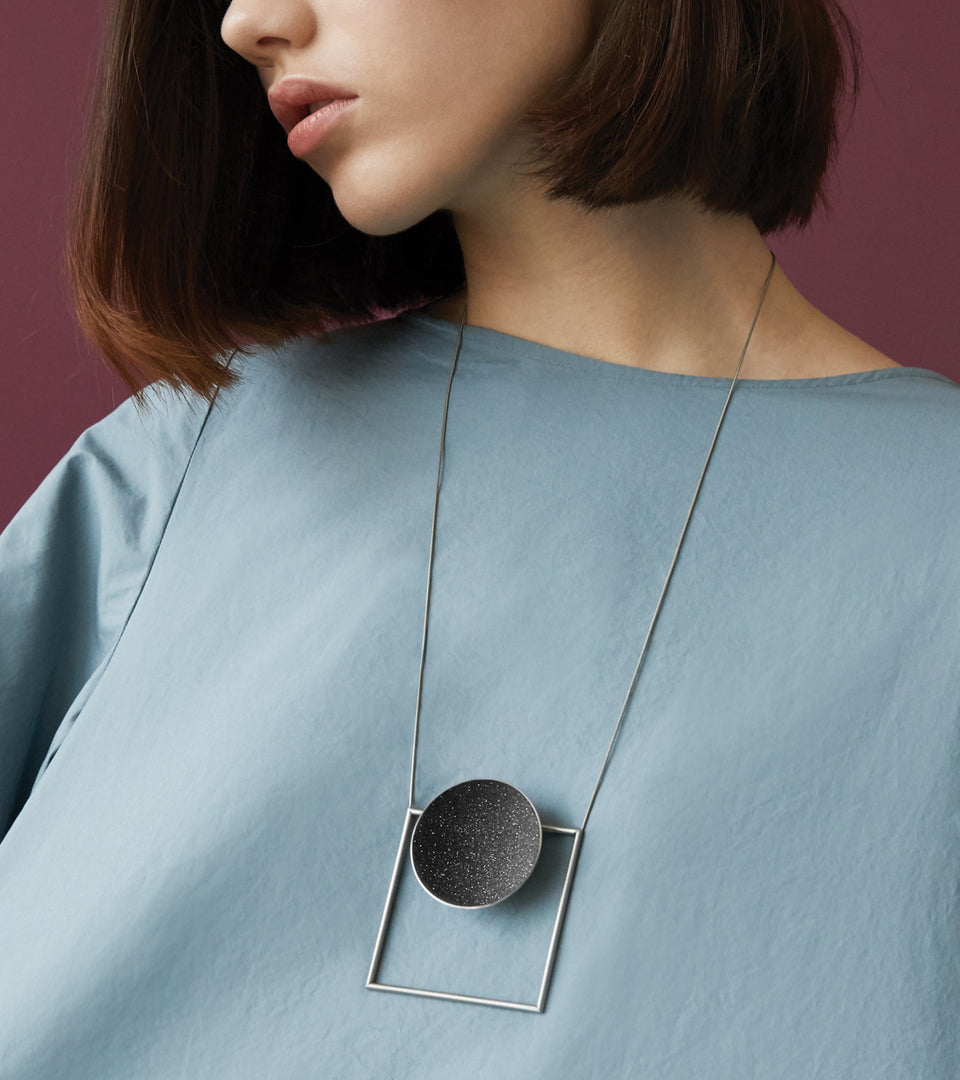 Contemporary necklace combines the geometry of a large stainless steel dome lined with the sparkle of diamond dust encrusted concrete suspended onto a minimalist steel square frame.