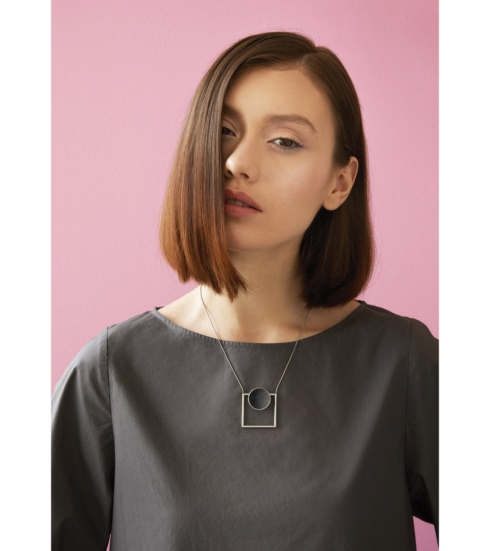 Continuum necklace combines the geometry of a smaller stainless steel dome lined with the sparkle of diamond dust encrusted concrete suspended onto a minimalist steel square frame.