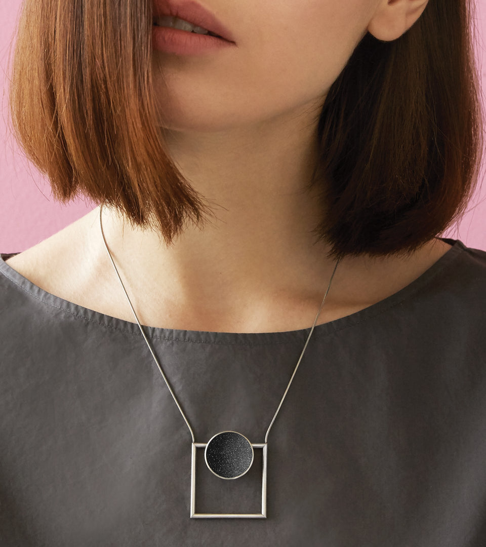 Minimalist necklace combines the geometry of a smaller stainless steel dome lined with the sparkle of diamond dust encrusted concrete suspended onto a minimalist steel square frame.