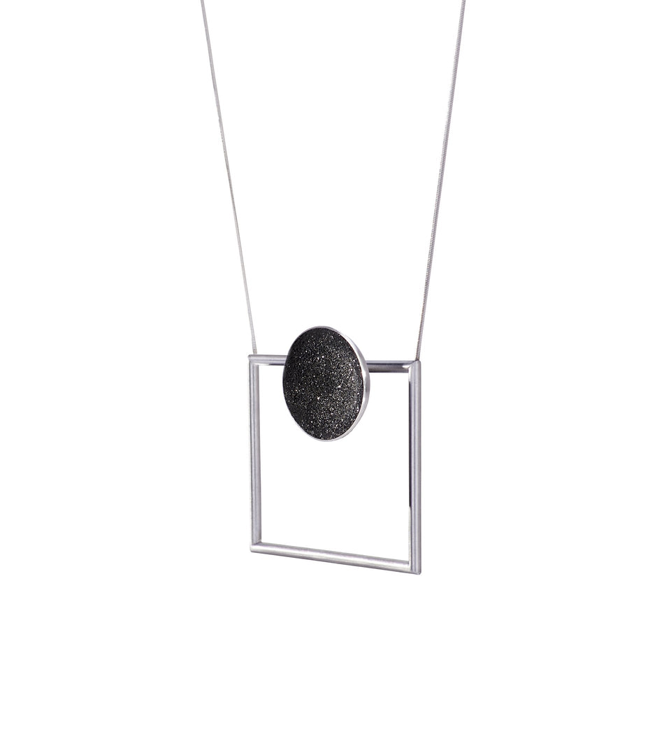 Modern necklace combines the geometry of a smaller stainless steel dome lined with the sparkle of diamond dust encrusted concrete suspended onto a minimalist steel square frame.