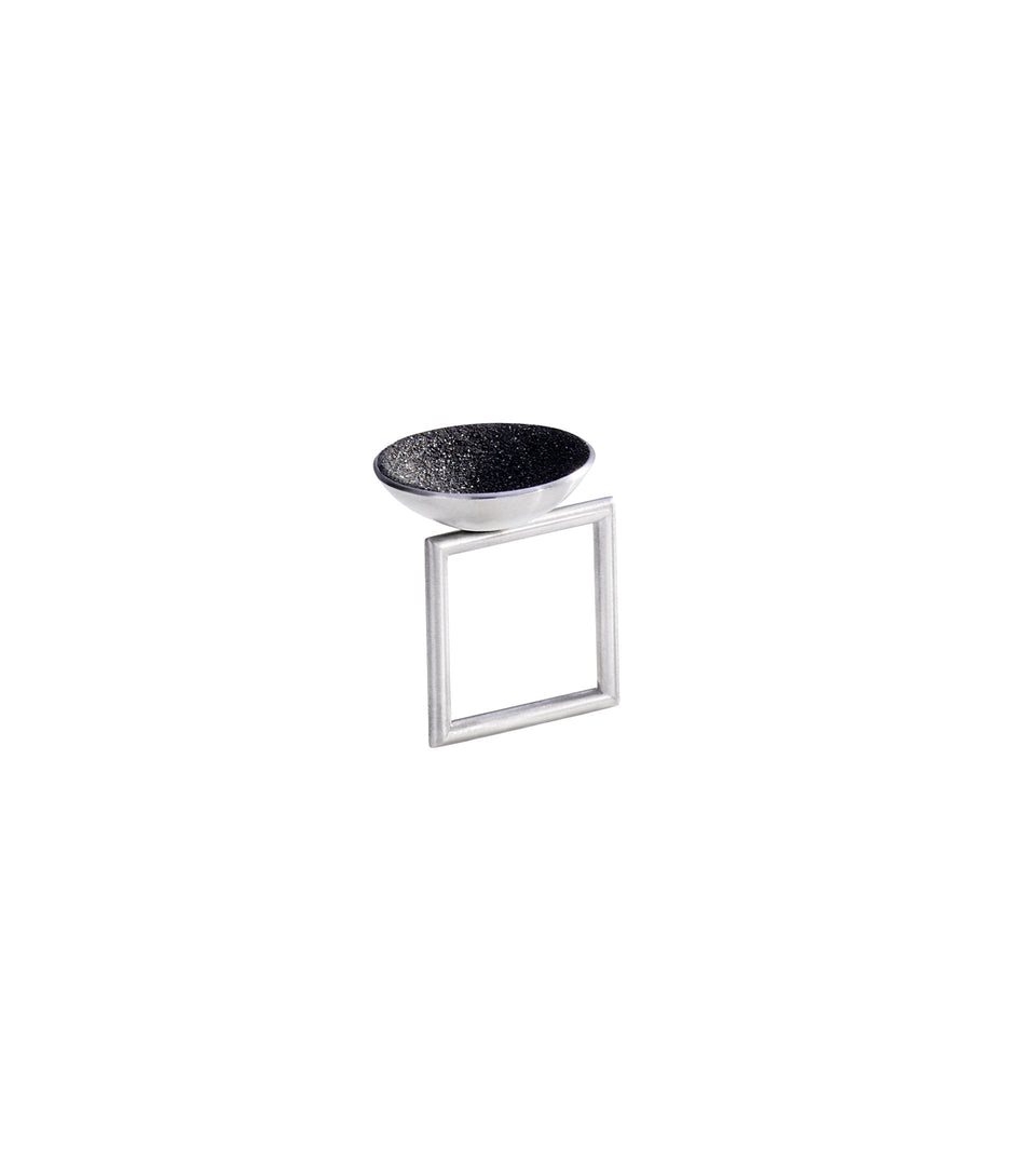 The Bauhaus design inspired Quadra ring is modern jewelry featuring diamond dust infused black concrete set into a thin stainless steel dome suspended from a steel minimalist square frame.