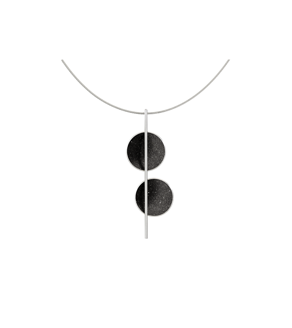 The minimalist Arago necklace sparkles with diamond dust infused black concrete set into two stainless steel domes and architecturally suspended onto an intersecting steel post and cable.