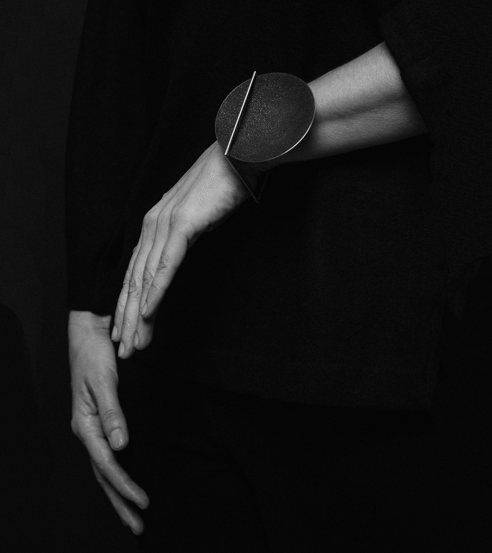 The minimalist Frama Max bracelet sparkles with diamond dust and black concrete set into a larger stainless steel dome architecturally suspended inside a minimalist steel square frame.