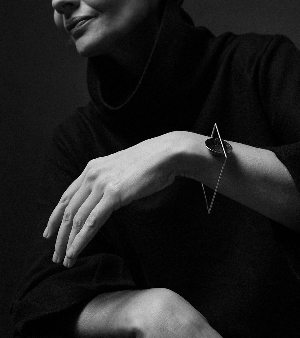 The Frama Minor bracelet is Bauhaus design inspired jewelry featuring diamond dust infused black concrete set into a small stainless steel dome suspended from a square steel frame.