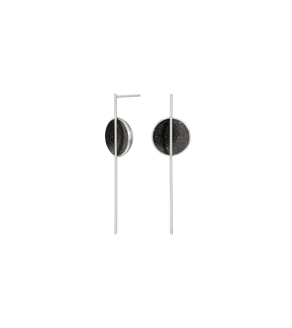 The Infini earrings sparkles with diamond dust and black concrete set into a stainless steel dome architecturally suspended behind a minimalist steel post.