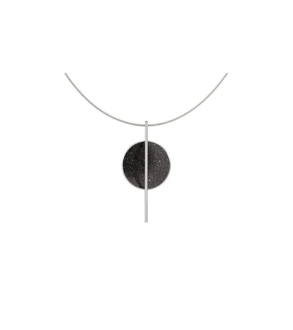 The Linnea necklace features black concrete and the sparkle of embedded diamond dust set into a stainless steel dome suspended from a steel post and hung by a stainless cable.