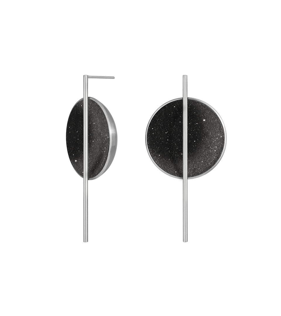 The Linnea Major statement earrings sparkle with diamond dust and black concrete set into a stainless steel dome architecturally suspended behind a minimalist steel post.