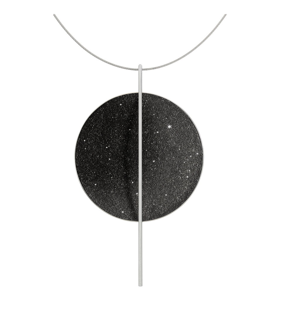 The statement Linnea Max necklace features black concrete and the sparkle of embedded diamond dust set into a large stainless steel dome intersected by a steel post and suspended by a stainless cable.