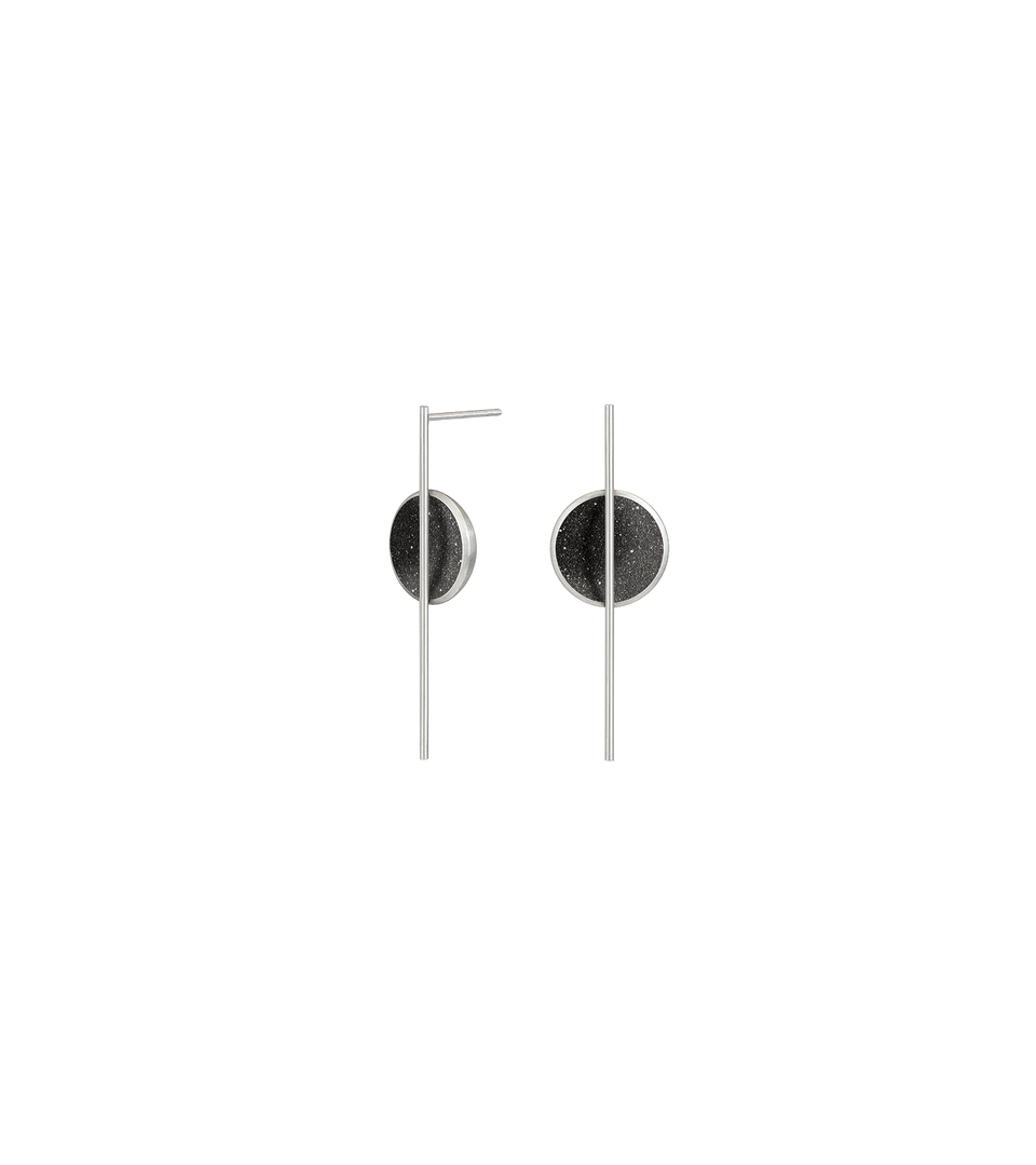 The minimalist earrings Linnea Minor sparkle with diamond dust and black concrete set into a stainless steel dome architecturally suspended from an elegant steel post.