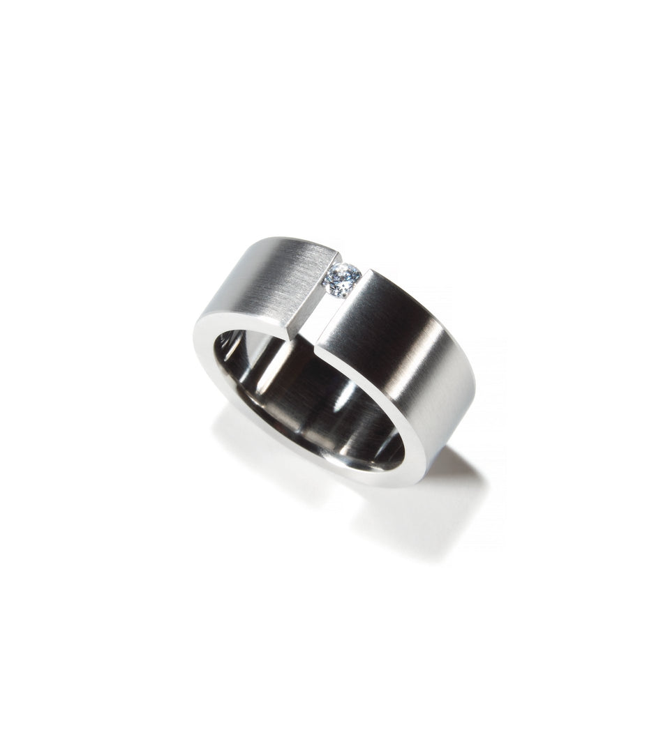 Top view engagement ring with .10ct diamond tension set into wide stainless steel band.