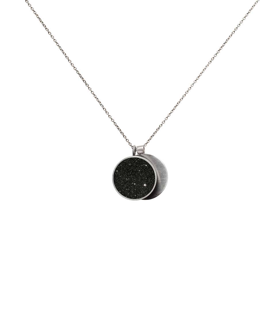This minimalist overlapping double pendant in concrete, diamond dust and stainless steel hangs from a linked necklace chain.
