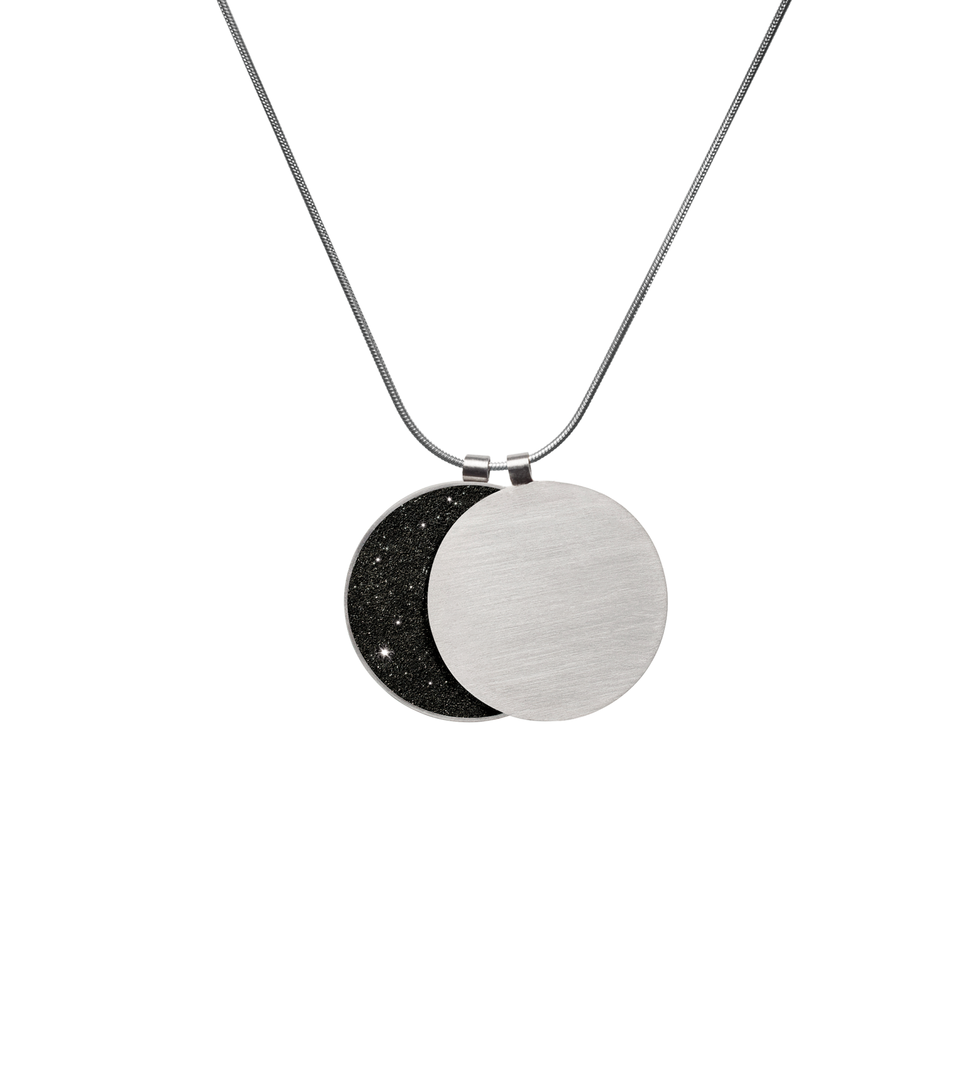 Classic and bold in style, this overlapping double pendant in concrete, diamond dust and stainless steel hangs centred creates the phases of the moon depending on how the piece hangs.