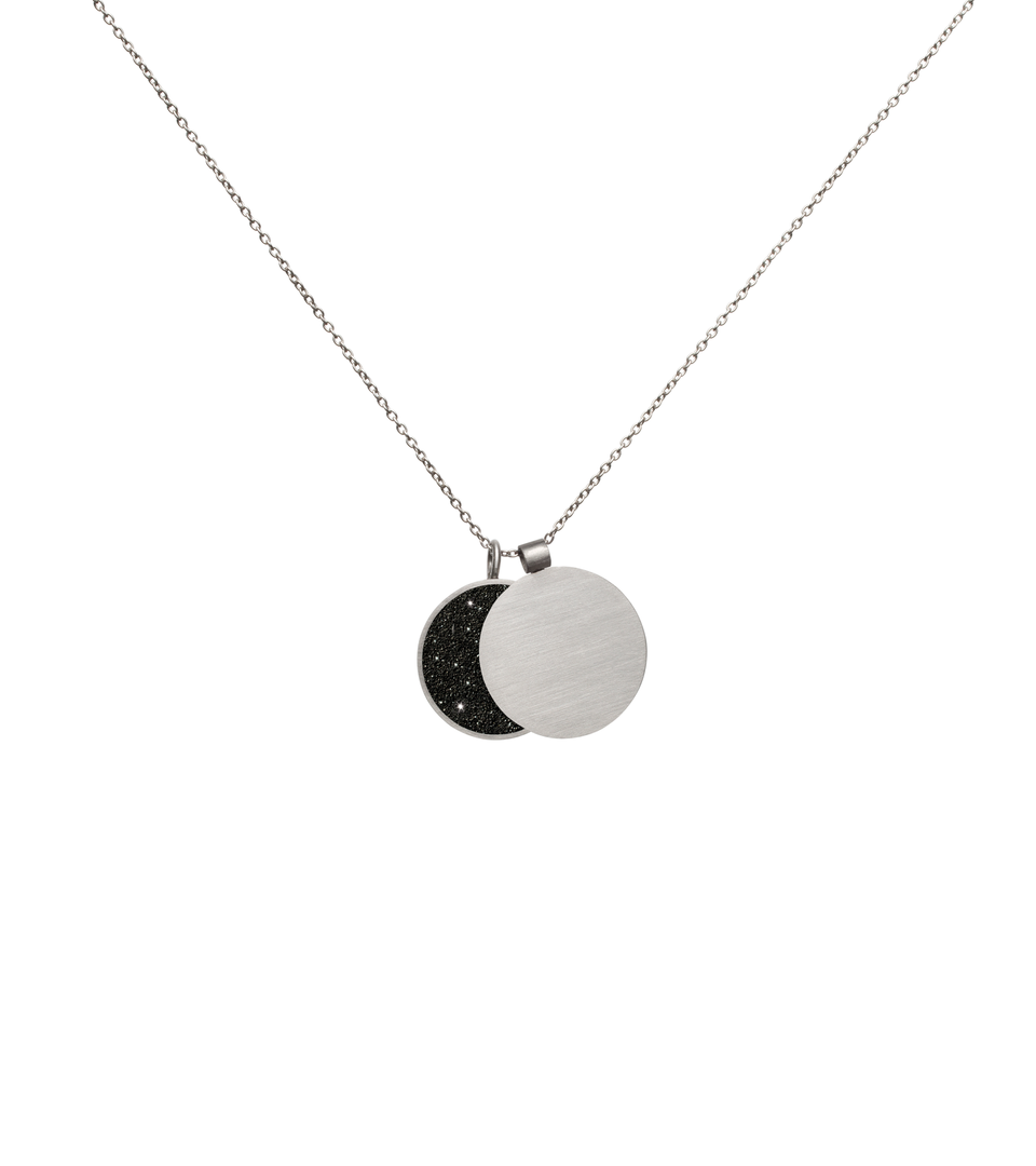 This minimalist overlapping double pendant in concrete, diamond dust and stainless steel hangs centred and shapes the phases of the moon depending on how the piece hangs.