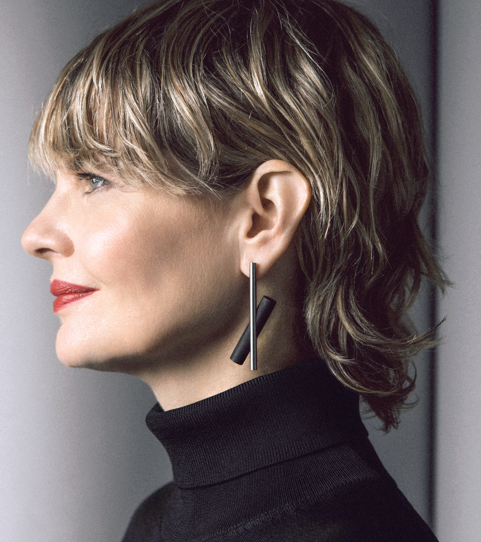 The modern design of the Unity x earrings (large) is highlighted by a natural or black concrete cylinder juxtaposed behind a brushed stainless steel rod.