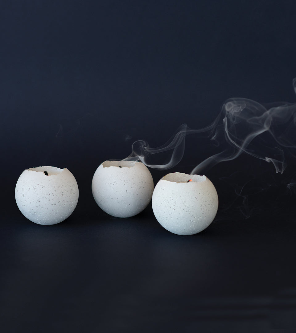White concrete tealight candles photographed on black.